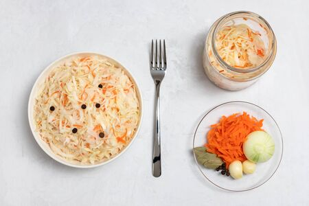 Homemade sauerkraut. Fermented food. Sauerkraut with carrots in a bowl and glass jar on a concrete white background. Vertical orientation. Top view, flat lay.