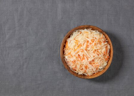 Homemade sauerkraut. Fermented food. Sauerkraut with carrots in a bowl on a gray background. Top view, flat lay. Copy space.