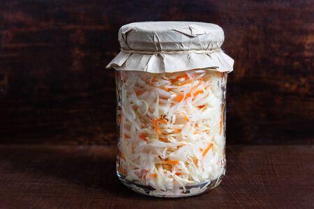 Homemade sauerkraut. Fermented food. Sauerkraut with carrots in a glass jar on a dark wooden background. Copy space.