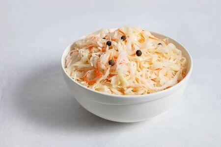 Homemade sauerkraut. Fermented food. Sauerkraut with carrots in a white bowl on a white background closeup.