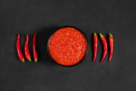 Hot chili pepper sauce paste harissa. Adjika on a black background. Traditional Tunisia, Georgian and Arabic cuisine. Homemade rose harissa in a bowl. Flat lay, top view.