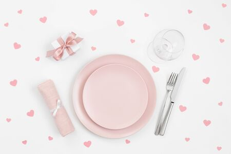 Pink table setting with pink confetti hearts, gift, napkin on a white background. Romantic or wedding dinner. Valentines day or mothers day background. Copy space, top view, flat lay.