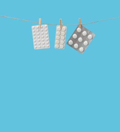 Blisters with pills hang on a clothesline on clothespins. Tablets isolated on a blue background. The health care concept. Space for text.