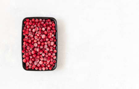 Frozen berries in a black plastic container on a white background. Vitamins. Frozen food. Copy space, top view, flat lay.