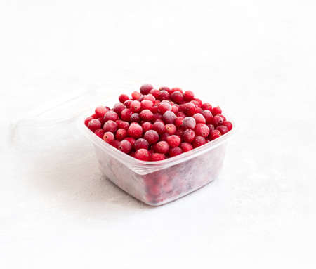 Frozen cranberries in a plastic container on a white background. Storage of frozen food. Side view. Фото со стока