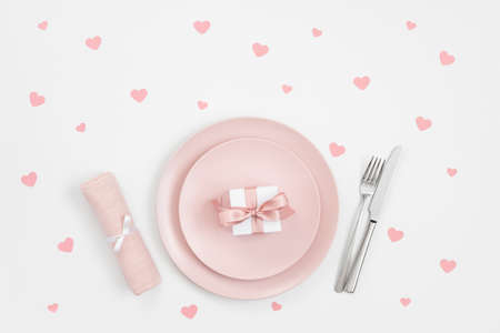 Romantic table setting with pink plate, gift and confetti hearts on white background. Love concept for Valentines or mothers day. Top view, flat lay.