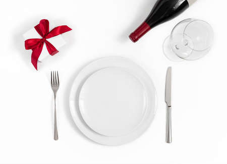 Festive table setting with a gift, wine and dishes on a white background. Romantic dinner concept for Mothers Day, Valentines Day and Christmas. Top view, flat lay.