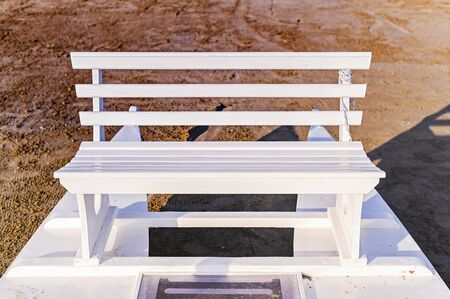 White wooden bench on the beach. Natural lighting street photo. Free space for text Imagens