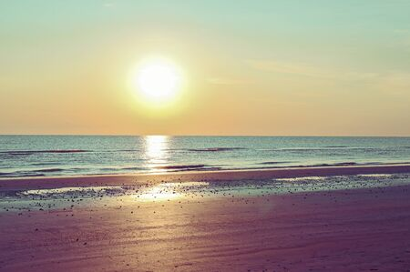 Sunset on the beach. Tinted photo in golden highlights. Sea and sandy beach. Banner, long format. Free space for text