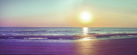 Sunset on the beach. Toned photo in blue and yellow highlights. Sea and sandy beach. Banner, long format. Free space for text