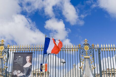 Gateway to the palace of Versailles. Flags at the main entrance and blue sky Редакционное