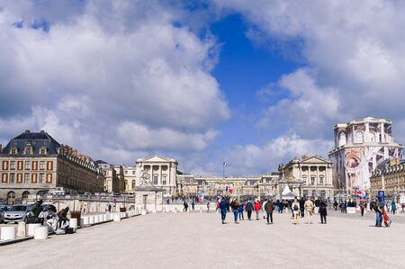 Gateway to the palace of Versailles. People at the main entrance and blue sky