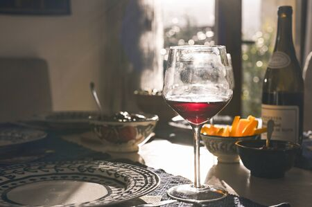Glass of wine on the dining table. Sun glare. Toned photo