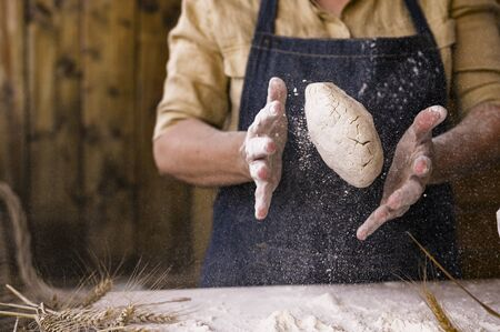 Women's hands, flour and dough. Levitation in the frame. A woman in an apron is preparing dough for home baking. Rustic style photo. Wooden table, wheat ears and flour in the crucifix. Emotional photo