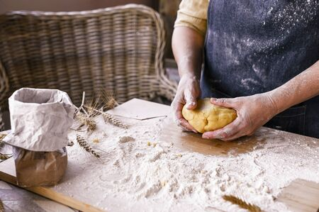 Female hands and dough. A woman is preparing a dough for home baking. Rustic style photo. Wooden table and flour. Free space for text