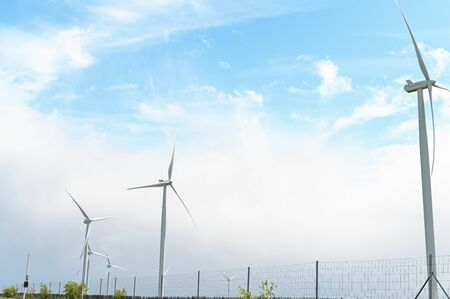 Windmills on a green field and blue sky. Green technologies in the modern world. Free space for text
