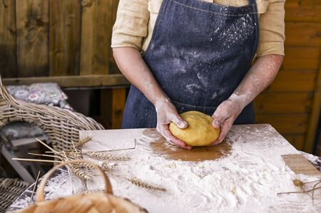 Female hands and dough. A woman is preparing a dough for home baking. Rustic style photo. Wooden table, wheat ears and flour. Free space for text