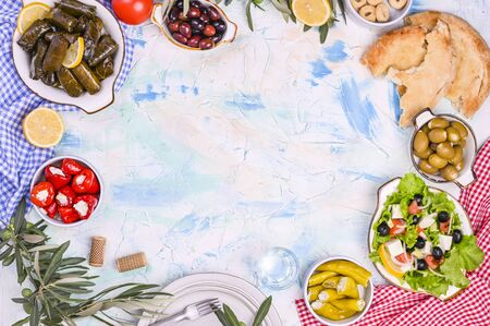 Turkish cabbage rolls and various snacks of national cuisine. Rice in grape leaves and olives. Food for a traditional oriental lunch. Free space for text, empty plate