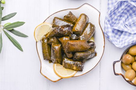 Traditional greek cuisine. Wrapped rice in grape leaves. Dolma with lemon and spices. Home cooked food