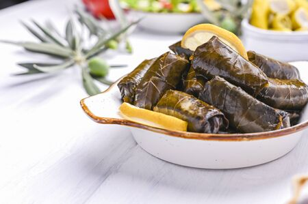 Traditional greek cuisine. Wrapped rice in grape leaves. Dolma with lemon and spices. Home cooked food. Olive branches and various spicy appetizers