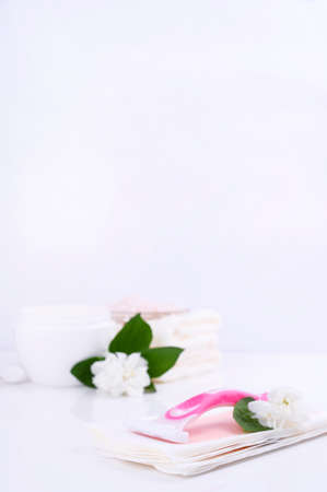 a set of different means for epilation on a colored background. Removal of unwanted hair. Body care products, towels, jasmine flowers, wax strips, razor. Minimalism. flatlay
