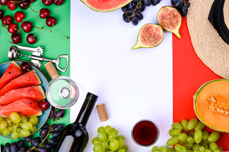 A bottle of wine, wineglass, grapes, different fruits and the flag of Italy. Country symbol backdrop. The concept of harvesting, august traditional summer vacation. Free space for text. Top view