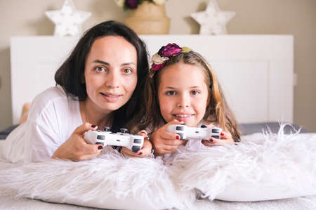 Little girl and mom are playing a computer game with mom. Jostics in hand. Modern computer games for children and parents. Dissemination of cheerful emotions by persons. High quality