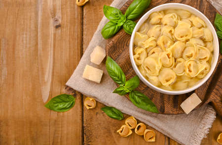 Tortellini mignon on a wooden board with basil and parmesan. Specialties of the cuisine from Bologna and Emilia Romagna: Cappelletti, fresh egg pasta with meat and vegetables filling. Copy space