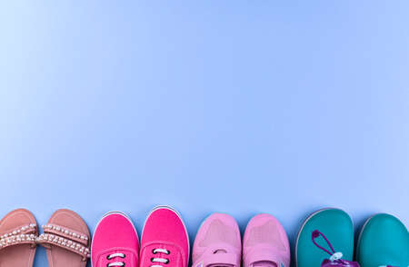 Pink sneakers, rubber boots and sandals for a girl on a blue background. Different shoes. Free space for text. Sale of childrens clothing. Top view