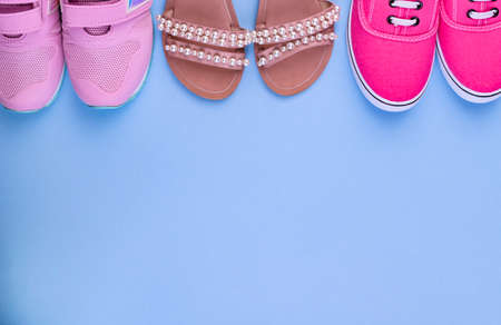 Pink sneakers and sandals for a girl on a blue background. Free space for text. Sale of childrens clothing. Top view