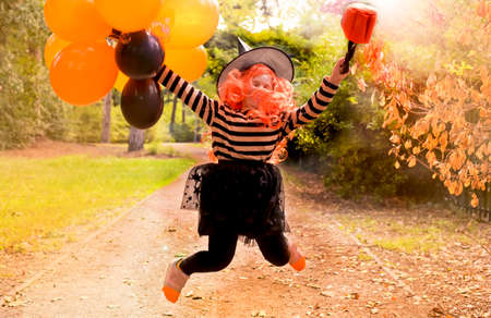 Little cheerful girl in a witch costume is jumping and having fun with balloons. Happy holiday Halloween. Sun glare in the frame. Soft focus on the main subject. Copy space. High quality photo 版權商用圖片