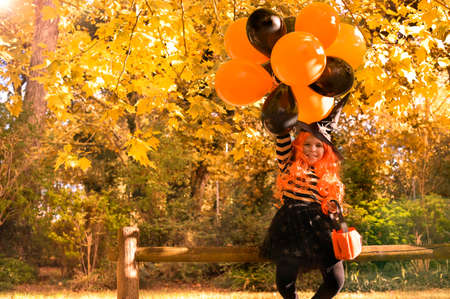 Happy Halloween. Child with big balloons, witch costume in autumn park. Soft changing focus on the main subject. Sun glare in the frame. High quality photo