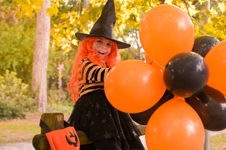 Little girl in a hat and witch clothes with big bright balloons is having fun in the autumn park. Soft changing focus on the main subject. Copy space. High quality photo
