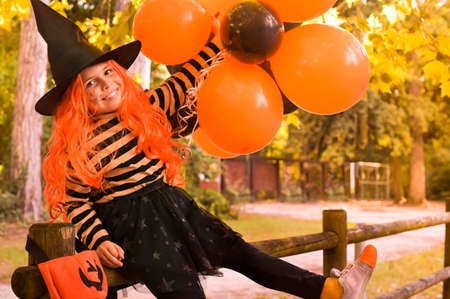 Happy Halloween. Little girl in a hat and witch clothes with big bright balloons is having fun in the autumn park. Soft changing focus on the main subject. Copy space. High quality photo