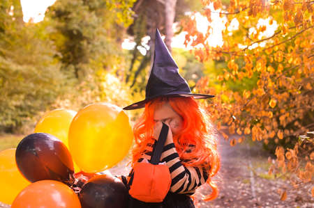 Sad Child in a carnival costume on Halloween with large colored balloons. Little girl in the autumn park. The focus is soft shifted on the main object. Copy space. High quality photo 版權商用圖片