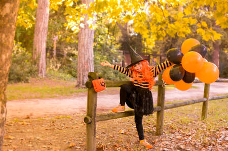 Little girl in the autumn park. A child in a witch costume on Halloween with large colored balloons. The focus is soft shifted on the main object. Copy space. High quality photo 版權商用圖片