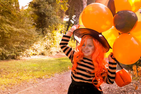 Halloween. Little girl in a hat and witch clothes with big bright balloons is having fun in the autumn park. Soft changing focus on the main subject. Copy space. High quality photo