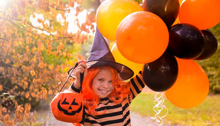 Halloween. A child in a carnival costume on Halloween with large colored balloons. Little girl in the autumn park. The focus is soft shifted on the main object. Copy space. Banner. High quality photo 版權商用圖片