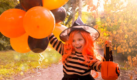 Halloween holiday. A child in a carnival costume on Halloween with large colored balloons. Little girl in the autumn park. The focus is soft shifted on the main object. Copy space. High quality photo