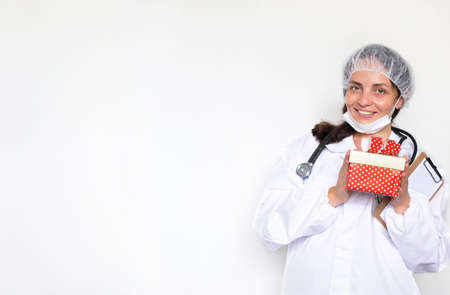 A woman doctor in a white coat, gloves and a mask holds a box of a gift for the New Year. Protection against infections during the COVID epidemic. Medicine concept. Focus on the face. Copy space. Stock Photo