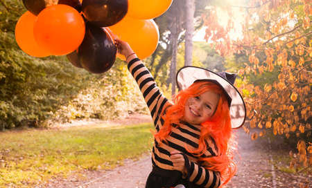 Halloween party. Cild in a carnival costume on Halloween with large colored balloons. Little girl in the autumn park. The focus is soft shifted on the main object. Copy space. Banco de Imagens