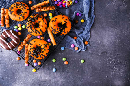 Halloween donuts on a gray stone background. Sweet pastries decorated for a horror party. Copy space. Top view. High quality photo. High quality photo
