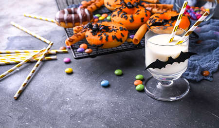 Halloween donuts and milk on a gray background. Sweet pastries and drinks decorated for a fun party. High quality photo