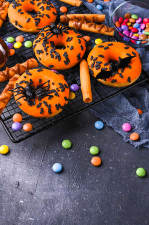 Sweet pastries decorated for a horror party. Halloween donuts on a gray stone background. Copy space. Top view. High quality photo. High quality photo
