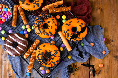 Halloween donuts on a wooden background. Sweet pastries decorated for a horror party. Copy space. Top view. High quality photo 免版税图像