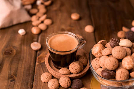 Dutch holiday Sinterklaas. Traditional sweets, cookies pepernoten and espresso on a wooden table. Copy space. High quality photo.