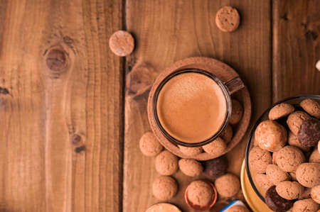 Traditional sweets, cookies pepernoten and espresso on a wooden table. Dutch holiday Sinterklaas. Copy space. Above Zdjęcie Seryjne