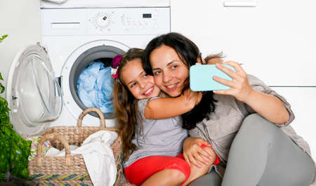 Happy mom and daughter talk via video call via phone, they take selfies and have fun. Good family relationships. MOM and a little girl in the room near the washing machine. Banner. Copy space