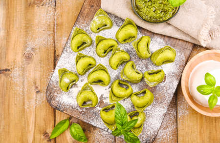 Tortellini e tortelloni typical italy. Food background with homemade raw Italian tortelloni and ingredients for green pesto on wooden background . High angle view. Copy space.