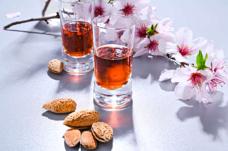 almond liquor. The traditional strong drink in italy to complete the dinner is a liqueur made from nuts and berries. Ratafia, alcohol in shot. top view on the table and blooming almonds. Copy space